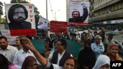 Pakistani protesters hold images of missing activist Salman Haider during a protest in Karachi on January 9.