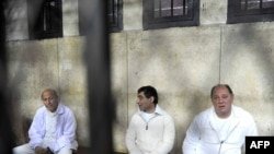 Former ministers Zuheir Garranah (right) and Ahmed al-Maghrabi (left) and former senior member of the National Democratic Party Ahmed Ezz (center) sit behind bars in Cairo in February.