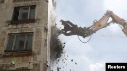 Russia -- An excavator wrecks a building, which is part of the old five-storey apartment blocks demolition project launched by the city authorities, in Moscow, Russia, June 20, 2017