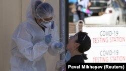 Медработник забирает мазок у пациента в пункте тестирования на коронавирус.