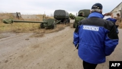 OSCE observers check a column of 15 MT-12 Rapira 100-mm antitank guns being withdrawn by Russian-backed separatists from Donetsk to the village of Zelene on October 28.
