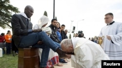 Pope Francis kisses the foot of a migrant during the foot-washing ritual at a refugee center near Rome late last month.