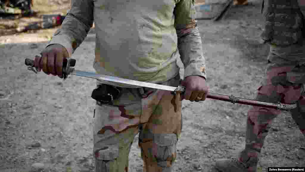 An Iraqi soldier with a sword he found in Mosul like those used by IS fighters for killing captives.