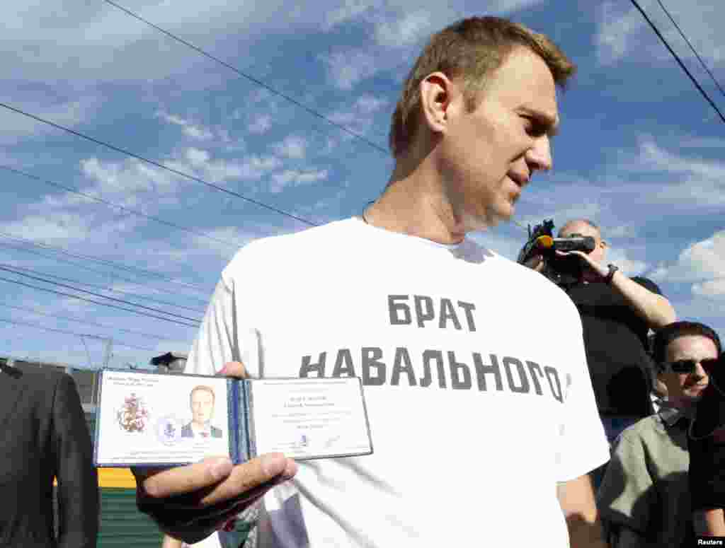 Russian anticorruption blogger Aleksei Navalny holds his Moscow mayoral candidate registration certificate before leaving boarding train from Moscow to Kirov where he is facing trial on embezzlement charges. (Reuters/Grigory Dukor)