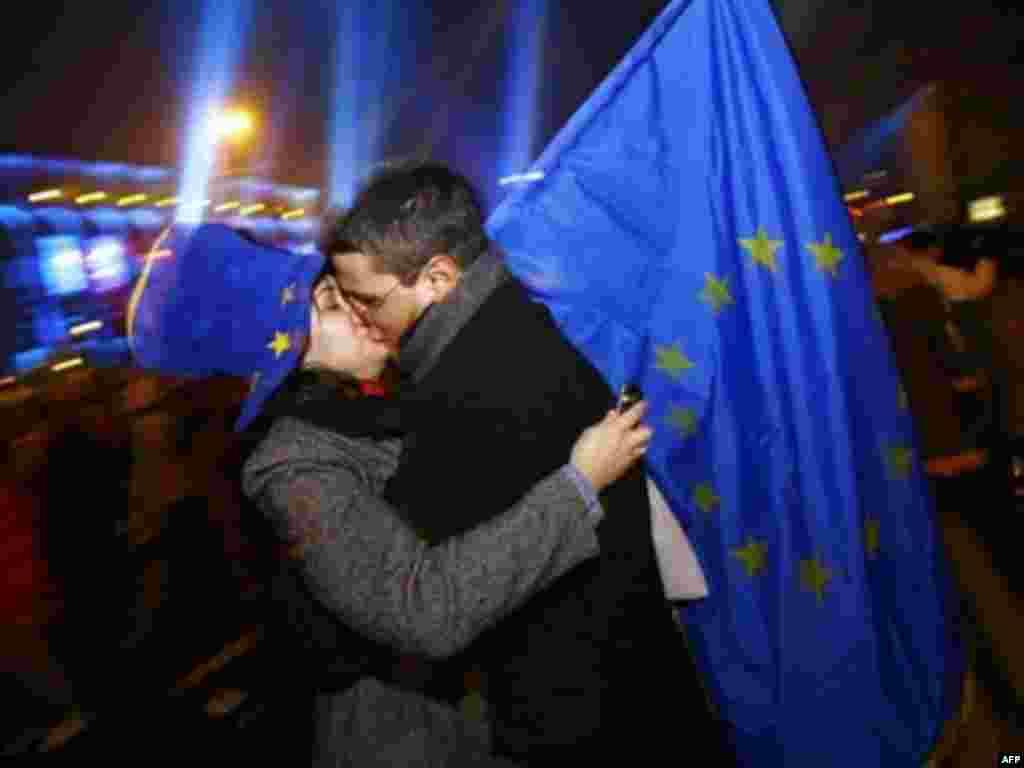Romania - A Romanian couple kiss each other after midnight as they hold an EU flag at a New Year celebration party in Piata Universitatii Square in Bucharest, 01Jan2007 - І січня 2007, Бухарест: тисячі болгарів та румунів зустріли Новий рік на святкових майданах як нові члени Європейського Союзу. На фото студенти Бухарестського університету святкують вступ Румунії до ЄС.