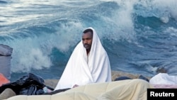 Италия жағалауында отырған мигрант. (Көрнекі сурет)