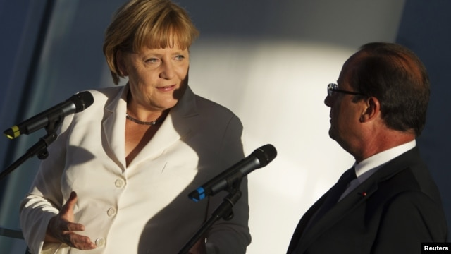 German Chancellor Angela Merkel (left) and France's President Francois Hollande address the media before talks at the Chancellery in Berlin on August 23.