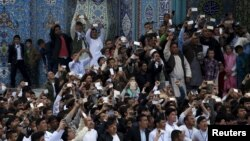 FILE: Afghans revers us use their mobile phones to capture the celebration of the Afghan New Year Norouz in Kabul.
