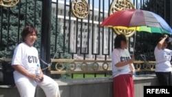 Ак үй алдына пикетке чыккан укук коргоочулар Төлөйкан Исмаилова, Азиза Абдрасулова жана Асия Сасыкбаева. Алар 2009-жылы 29-июлда шайлоодон кийин акцияга чыккан адамдарды камоолорго каршылыктарын билдиришкен. Бул шайлоодо Алмазбек Атамбаев Курманбек Бакиевге башкы атаандаш болгон. 31-июль, 2009-жыл