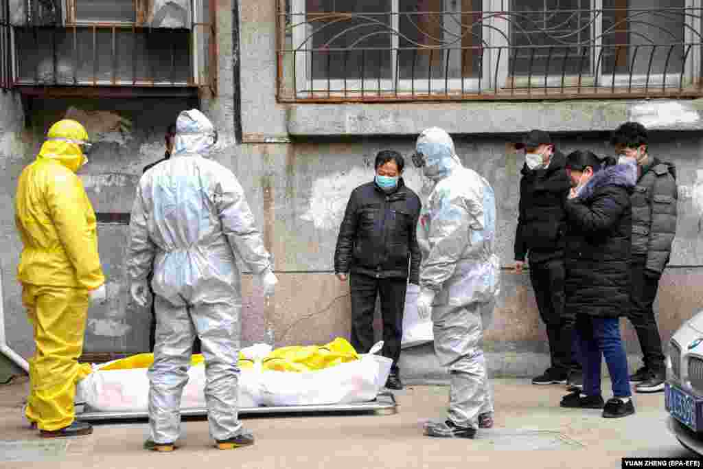 Funeral house workers take the body of a resident, who reportedly died because of the novel coronavirus (2019-nCoV) at home, out of a residential building in Wuhan, in central China's Hubei province, February 1, 2020.