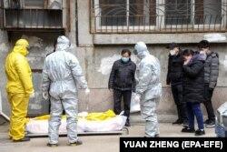 Родственники и работники похоронного дома в Ухане забирают тело человека, умершего от COVID-19, 1 февраля 2020 года