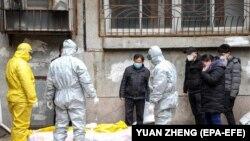 Работники похоронного агентства забирают тело покойного, умершего дома от коронавируса. Китай, Ухань, февраль 2020 года