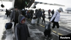 Russia -- Russian citizens, who were evacuated from Libya, leave a plane owned by the Emergency Situations Ministry as they walk along a landing runway at Domodedovo airport outside Moscow, 23feb2011