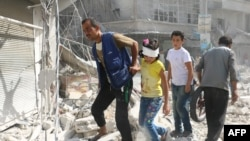 Syrians walk over rubble following air strikes on the rebel-held Fardus neighborhood of the embattled Syrian city of Aleppo on October 12.