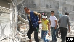 Syria - Syrians walk over rubble following air strikes on the rebel-held Fardous neighbourhood of the northern embattled Syrian city of Aleppo October 12, 2016