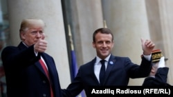 U.S. President Donald Trump and French President Emmanuel Macron gesture as they meet at Elysee presidential palace.