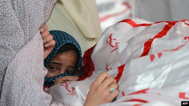 A child reacts as Shi'ite Hazaras gather around the coffin of a bomb victim on the third day of protests following the bombing in Quetta on February 19.