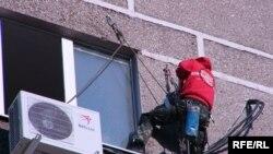 Спортсмен-экстремал на своем пути к вершине многоэтажного дома в городе Актобе.