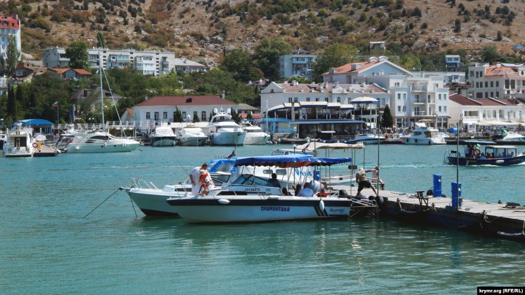 По обеим сторонам бухты пришвартованы морские прогулочные катера