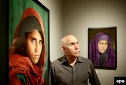 Стів МакКаррі поруч із фото Шарбат (л) на виставці його праць у Німеччині, 2013 рік