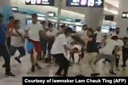 """""""Белые футболки"""" избивают протестующих на одной из платформ метро Гонконга. 18 июля 2019 года"""