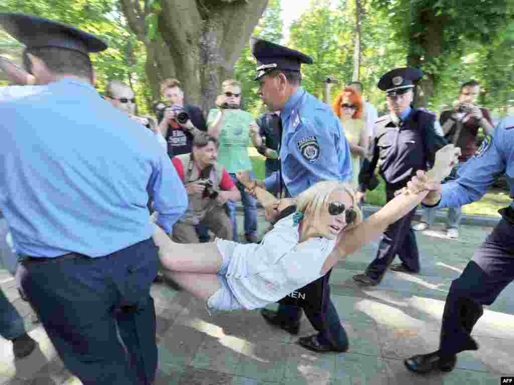 Police officers carry an arrested activist of the FEMEN feminist movement after a rally in front of the parliament in Kyiv. More than 1,000 people protested in front of the Ukrainian parliament against President Viktor Yanukovych's unpopular economic policies.Photo by Genya Savilov for AFP