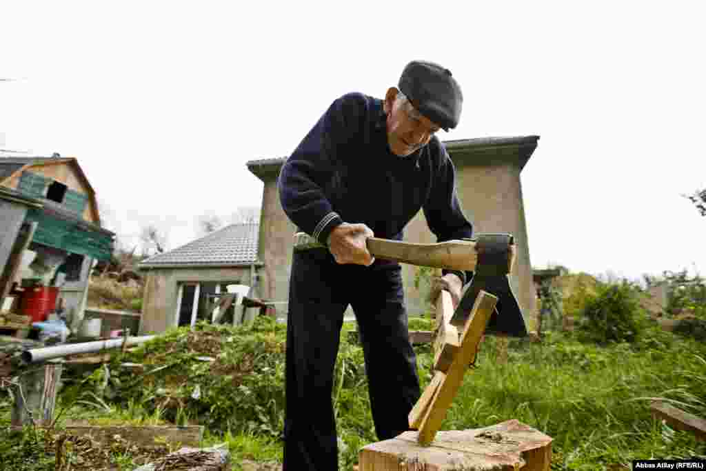 Kalayzhan's 89-year-old husband chops wood behind their house.