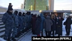 Группе матерей, не согласных с изменением правил предоставления социальной помощи, проход к администрации президента Казахстана блокирует шеренга полицейских. Нур-Султан, 18 декабря 2019 года.