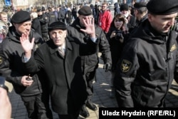 An elderly man is detained by police in Minsk.