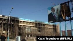 """""""Өзенмұнайгаз"""" компаниясының өртеніп кеткен ғимараты мен Назарбаевтың жарнамасы. Жаңаөзен, 19 желтоқсан 2011 жыл."""