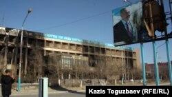 Пострадавшее здание офиса компании «Озенмунайгаз» и испорченный билборд с изображением президента Нурсултана Назарбаева. Город Жанаозен Мангистауской области, 19 декабря 2011 года.