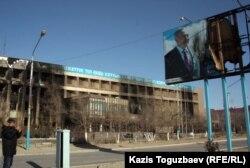 """Пострадавшее здание офиса компании """"Озенмунайгаз"""" и испорченный билборд с изображением президента Нурсултана Назарбаева. Город Жанаозен, 19 декабря 2011 года."""