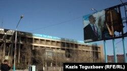 """Обгоревшее во время декабрьских событий прошлого года здание офиса компании """"Озенмунайгаз"""" и испорченный билборд с изображением президента Нурсултана Назарбаева в Жанаозене."""