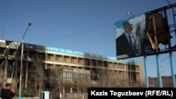 Пострадавшее здание офиса компании «Озенмунайгаз» и испорченный билборд с изображением президента Назарбаева. Жанаозен, 19 декабря 2011 года.
