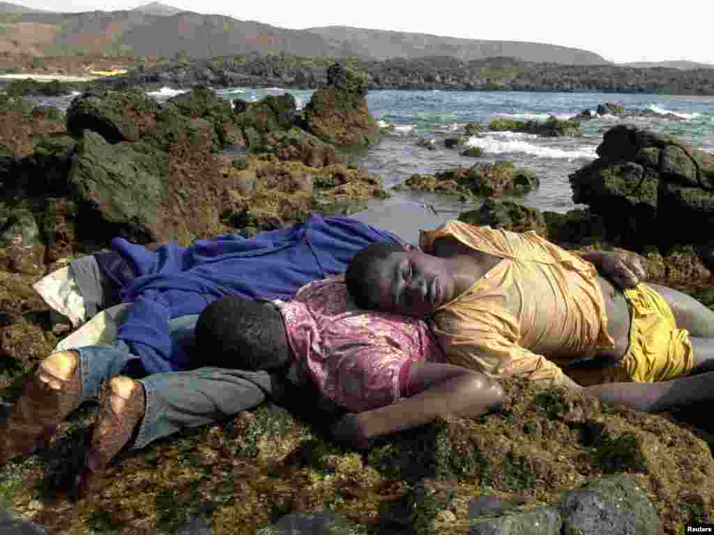 Drowned African immigrants lie on the coast in Fuerteventura, one of the Spanish Canary Islands off the coast of Morocco August 1, 2003. Six immigrants drowned, when their flimsy boat ran aground and 15 others disappeared on Thursday when their boat capsized six miles offshore. Fuerteventura is the nearest of the Canary Islands to the African coast and traffickers habitually head for its shores from launching points in southern Morocco, packing their passengers into overloaded boats. REUTERS/Juan Medina