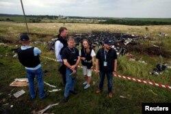 Эксперты ОБСЕ возле участка, где лежат обломки сбитого самолета