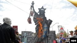 FILE - Pro-government demonstrators burn anti US and Israeli effigies during a rally marking Al-Qods Day (Jerusalem Day), in support of Palestinian resistance against Israeli occupation, in Tehran, July 1, 2016.