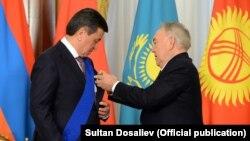 Nursultan Nazarbayev (solda) Qırğızıstan prezidenti Sooronbay Jeenbekovu təltif edir