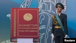 Солдат стоит рядом с макетом Конституции Казахстана. Алматы, 30 августа 2014 года.