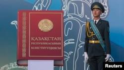 Военнослужащий стоит рядом с макетом Конституции Казахстана. Иллюстративное фото.