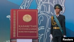 Қазақстан конституциясы макетінің жанында тұрған әскери қызметкер. Алматы, 30 тамыз 2014 жыл.