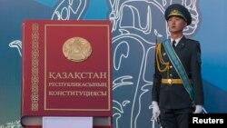 Военнослужащий рядом с макетом Конституции Казахстана. Алматы, 30 августа 2014 года.