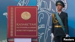 Қазақстан конституциясын бейнелейтін макет кітаптың жанында тұрған сарбаз. Алматы, 30 тамыз 2014 жыл. (Көрнекі сурет)