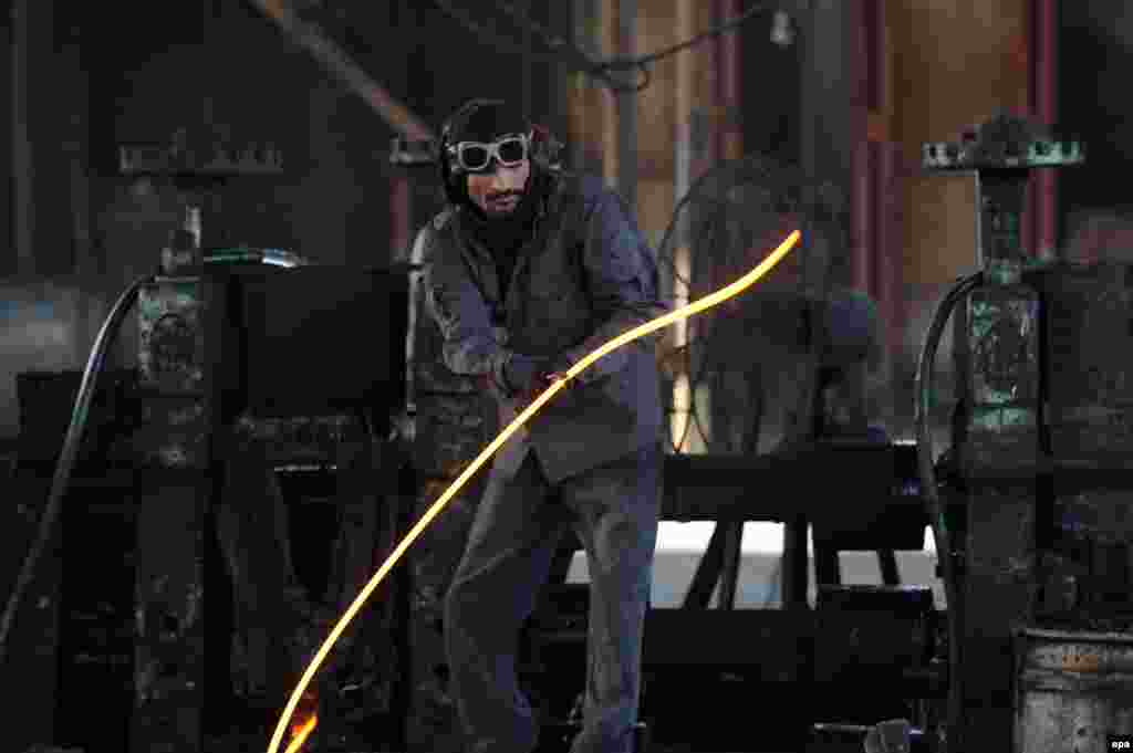 An Afghan worker holds a molten iron rod at a factory in Jalalabad. (epa/Ghulamullah Habibi)