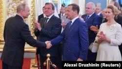 Ռուսաստանի նախագահ Վլադիմիր Պուտինին երդմնակալության արարողության ավարտին շնորհավորում են վարչապետ Դմիտրի Մեդվեդևը և Գերմանիայի նախկին կանցլեր Գերհարդ Շրյոդերը, Մոսկվա, Կրեմլ, 7-ը մայիսի, 2018թ․