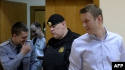 Aleksei Navalny (right) enters the court room for the verdict.