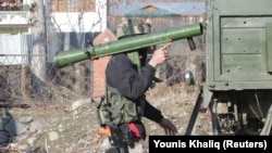 An Indian Army soldier carries a rocket launcher near the site of a gunbattle between suspected militants and Indian security forces in Pinglan village in south Kashmir's Pulwama district on February 18.