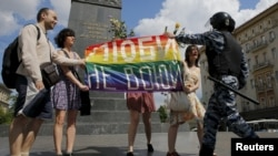 Participants hold a rainbow flag as a policeman stops them during an LGBT community rally in central Moscow on May 30, 2015.
