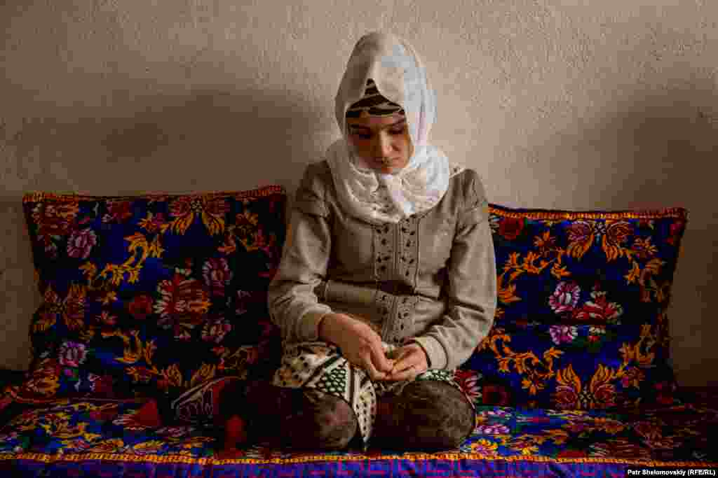 Zarina Yunusova in the living room of her parents' house in the town of Obigarm in Tajikistan.