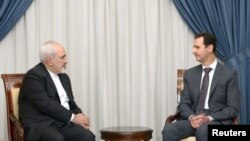 Syria's President Bashar al-Assad (R) meets with Iranian Foreign Minister Mohammad Javad Zarif in Damascus, Syria, in this handout photograph released by Syria's national news agency SANA on August 12, 2015.